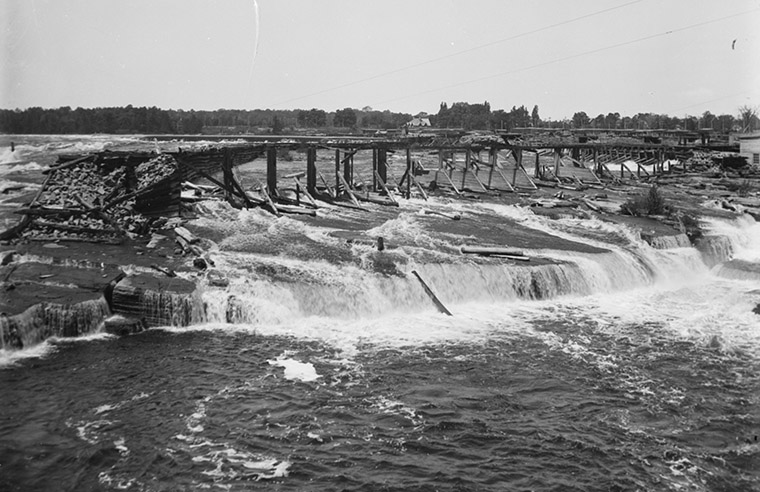 """The Hurdman Wing Dam, Chaudière Falls. Looking north-west over """"Table Rock,"""" March 1902. Photo credit: Topley Studio / Library and Archives Canada."""