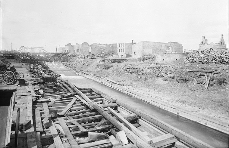 Ruins for Mr. Bronson after the Great Ottawa-Hull Fire of 1900. Booth Street Bridge visible in the distance. Photo credit: Topley Studio / Library and Archives Canada.